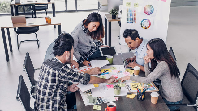 Female Creative director team leader brainstorm branding project with designer team at meeting table.discussion idea in creative office.