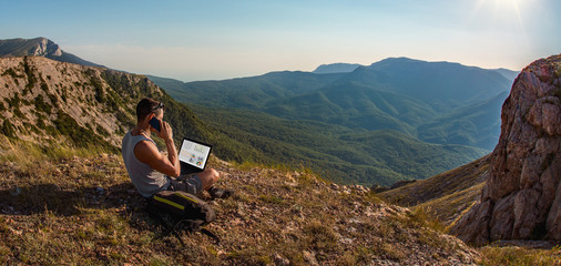 man freelancer with laptop, call by cellphone, on beauty mountains landscape