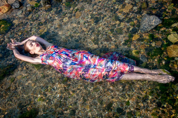 The fashion model lies on the rocks and poses in the sea water.