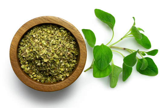 Dried chopped oregano in dark wood bowl next to fresh oregano leaves isolated on white from above.