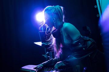 blonde stylish dj girl touching dj equipment in nightclub Wall mural