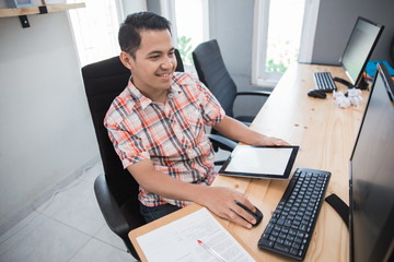 busy asian man working in his office using tablet and pc at the same time