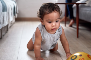 Baby crawling on floor at home