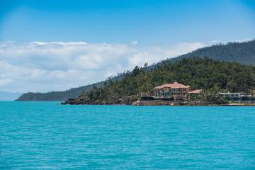 Urlaubsinsel in türkis farbenem Meer mit leichter Bewölkung am Himmel