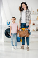 daughter in pink t-shirt standing near smiling mother in grey shirt with basket and in laundry room