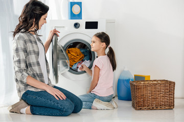 daughter in pink t-shirt and mother in grey shirt sitting on floor near washer with clothes in laundry room