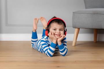 Young boy lying on floor with headphones