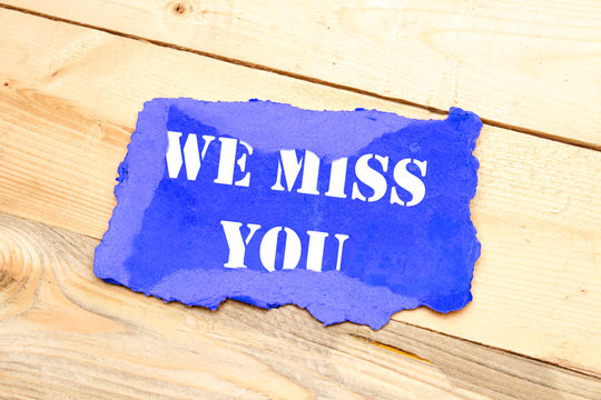 Text We miss you appearing on blue cardboard