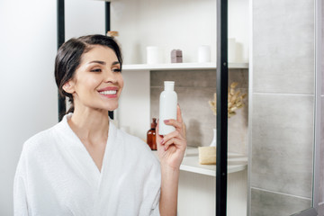 woman in white bathrobe looking to mirror, holding bottle with lotion and smiling in bathroom