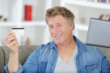 mature man using his laptop and holding his credit card
