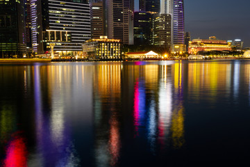 Downtown Singapore during the blue hour with the city lite up and reflecting in Marina bay below.