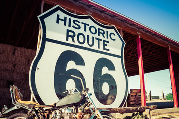Stores photo Route 66 A large Route 66 road sign with a weathered motorcycle in the foreground.