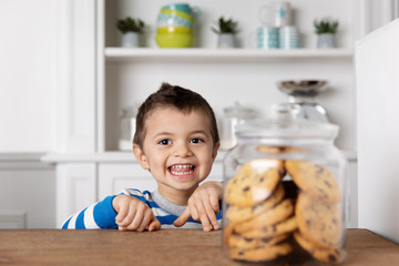Happy young boy at kitchen table next to cookie jar