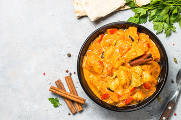 Chicken tikka masala with rice on black top view.
