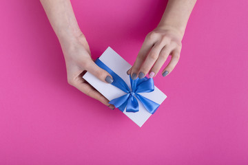girl holding a beautiful present in hands, women with gift box with a tied blue ribbon bow in hands on a colored pink cardboard background, top view, concept holiday, love and care