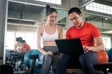 Trainer and lady client discussing her progress in computer at the gym