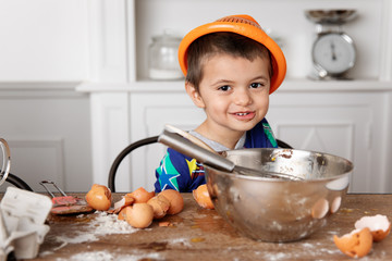 Silly with colander on head baking at kitchen table