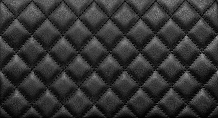Close-up texture of genuine leather with black rhombic stitching
