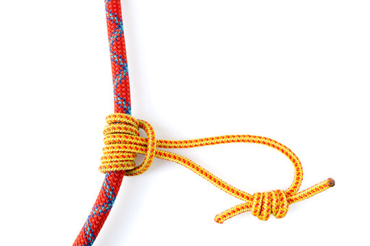 Prusik Knot or Triple Sliding Hitch formed with a 5mm yellow Prusik loop around a 9.8mm red climbing rope. This friction hitch is used in climbing, canyoneering, mountaineering, caving, rope rescue.