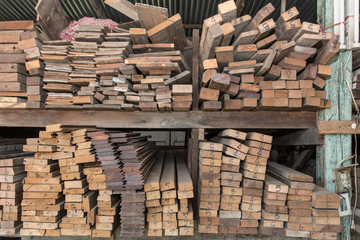 Piles of old wooden boards in the sawmill,  Warehouse for sawing boards on a sawmill indoors. Wood timber stack of wooden blanks construction material. Industry, Vintage styles