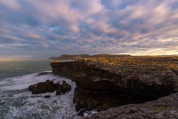 Rocky coast of Ajo Cape at sunset, Cantabria, Spain