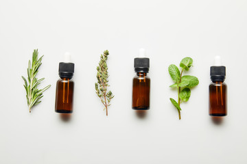 Wall Murals Condiments Flat lay with herbs and bottles with essential oil on white background