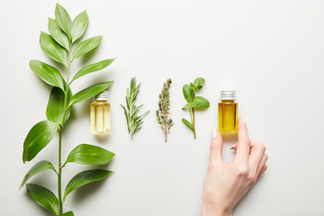 Cropped view of woman holding bottle with essential oil on white background