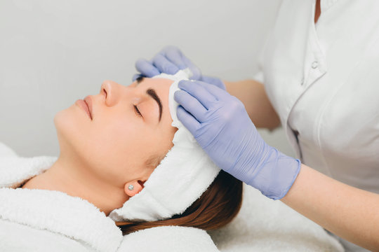 beautician wiping face to her patient before skin treatment