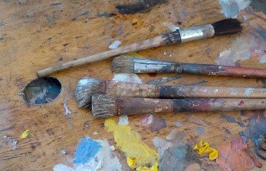 Old brushes and paints on a dirty palette in the artist's studio