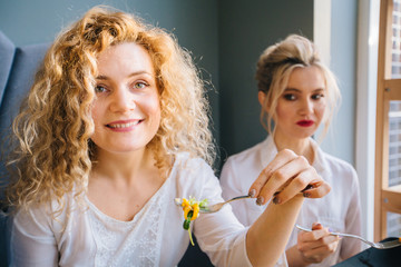 Blond curly american woman eating salad in cafe or restaurant with friend