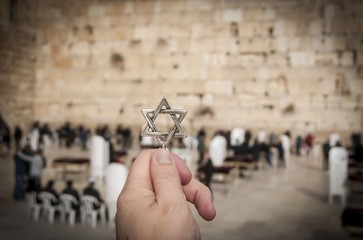 JERUSALEM, ISRAEL. February 15, 2019. Hand holding a Star of David, a Jewish national and religious symbol in front of the Western wall of the Jewish Temple in the Old city of Jerusalem.