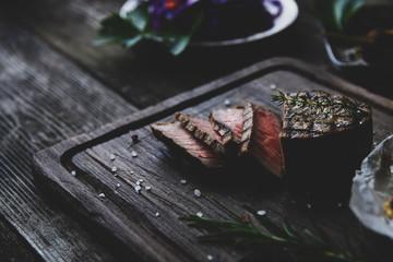 Fleisch Steak auf einem Alte Schneidbrett mit dunkel hintergrund Salz und Kräuter