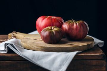 un bodegón con tres tomates maduros sobre una tabla de madera