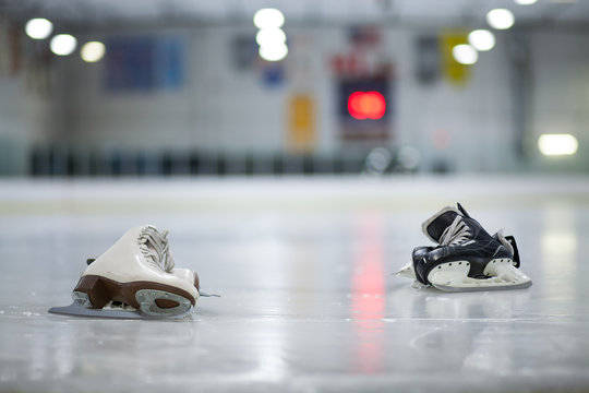 Figure Skates and Hockey Skates on Ice Rink