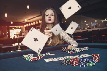 Young woman throwing playing cards in casino