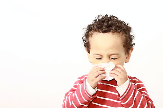 child blowing nose after catching a cold with white background stock photo