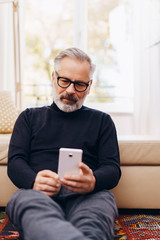 Attractive bearded senior man using a mobile phone