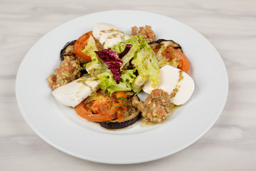 White cheese salad with tomato, eggplant and cabbage on a plate.