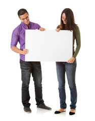 Cheerful Young Couple Look Down At Blank Poster