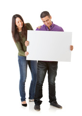 Young Couple Looks Down At Blank White Card