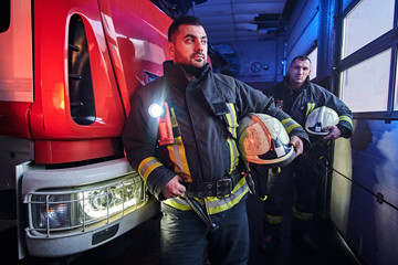 Two firemen wearing protective uniform standing next to a fire engine in a garage of a fire department.