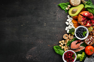 Healthy food: Fish, blueberries, nuts, pomegranate, avocados, tomatoes, spinach, flax. Concept of Dietary Nutrition. Top view.