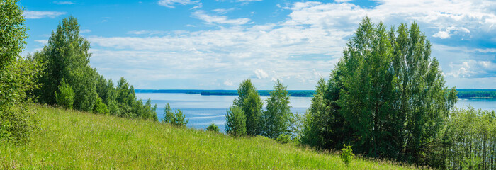 Panoramic view from green hill to Kama river sky with clouds.