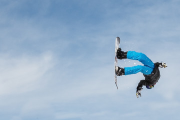 Snowboarder (boy, male) doing an acrobatic backflp after a jump.  With copyspace and blue sky.
