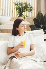 Cute woman wearing while t-shirt drinking orange juice at the bed