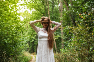 A woman in the forest covering her eyes with her hair