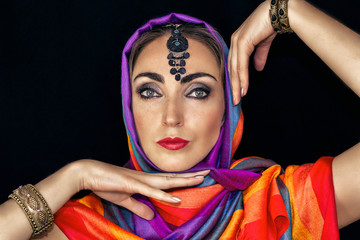 East woman in burqa with jewels on a black background. A woman in a bright scarf is dancing.