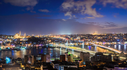 Panoramic view of Bosphorus with lots of illuminated bridges and mosques. Istanbul cityscape at night with cloudy sky. Touristic famous place of Turkey