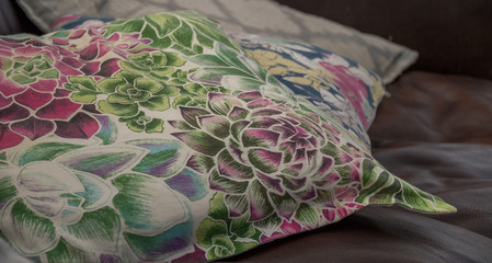 Cushions with a flower motif scattered on a brown leather couch image in landscape format with copy space