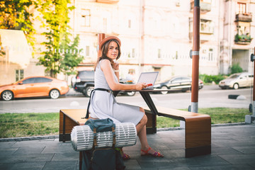 theme tourism and travel young student. beautiful young Caucasian girl in dress and hat sits in street cafe at wooden table using laptop technology and mobile phone. Search and book hotel and ticket